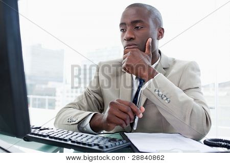Serious entrepreneur while working with a computer in his office