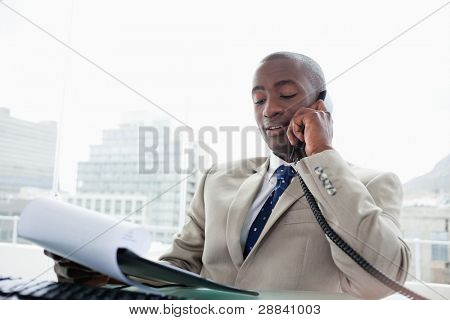 Businessman on the phone while reading a document in his office