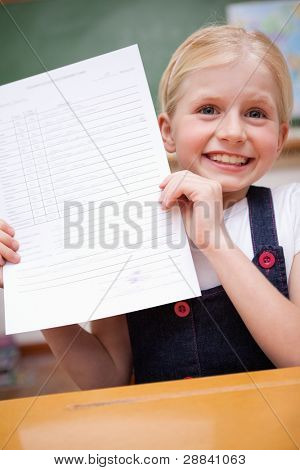Portrait of a girl showing her school report in a classroom