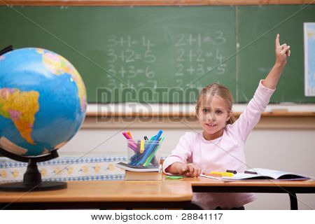 Cute schoolgirl raising her hand to answer a question in a classroom