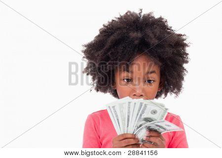 Niña mirando billetes de banco contra un fondo blanco