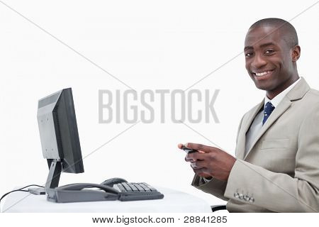 Smiling businessman sending a text message against a white background