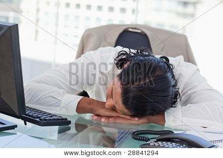 Tired businessman sleeping on his desk in his office