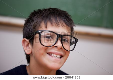 Close up of a smiling schoolboy in a classroom