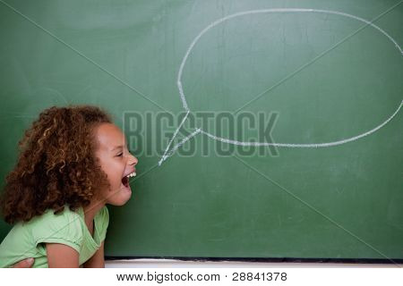 Schoolgirl posing with a speech bubble in a classroom