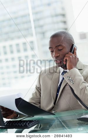 Portrait of a serious entrepreneur making a phone call while reading a document in his office