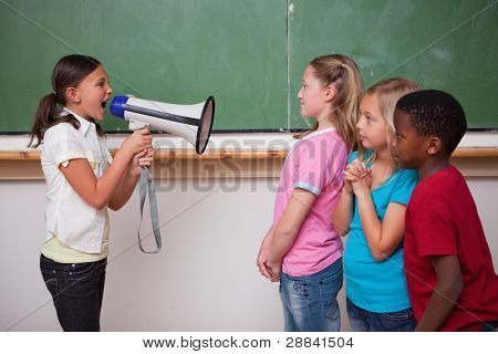 Angry schoolgirl screaming through a megaphone to her classmates in a classroom
