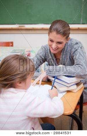 Portrait of a schoolgirl writing with her teacher in a classroom
