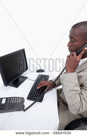 Side view of a secretary answering the phone while using a computer against a white background