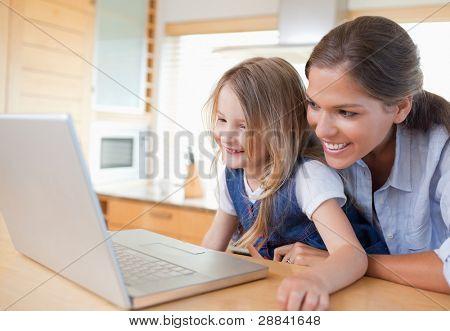 Sonriente de la madre y su hija con un cuaderno en su cocina