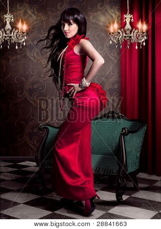 beautiful woman in evening dress standing in front of an victorian chair