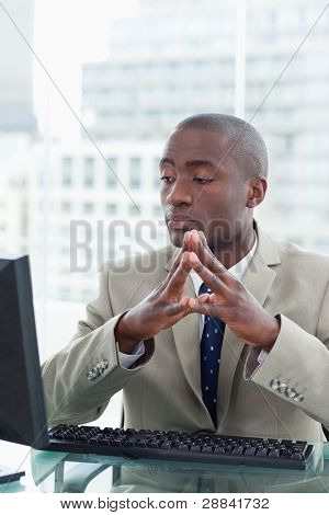 Portrait of a serious office worker using a computer in his office