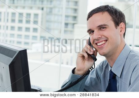 Happy office worker on the phone in his office