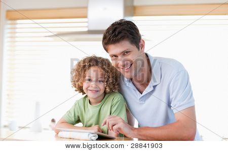 Smiling boy and his father using a tablet computer in their kitchen