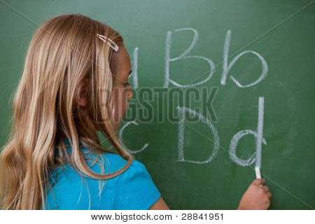 Schoolgirl writing letters on a blackboard