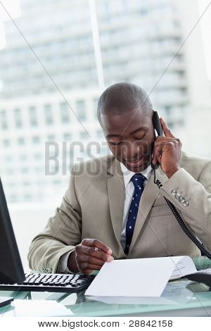 Portrait of an entrepreneur making a phone call while reading a document in his office
