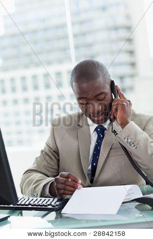 Retrato de un empresario realizar una llamada telefónica al leer un documento en su oficina