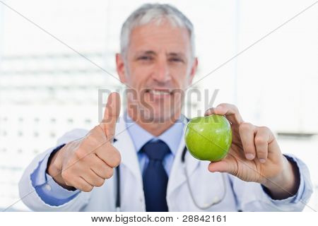 Doctor showing an apple with the thumb up in his office