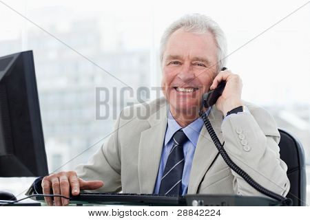 Smiling senior manager on the phone in his office