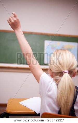 back view of a schoolgirl raising her hand in a classroom