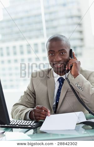 Portrait of a smiling entrepreneur making a phone call while reading a document in his office