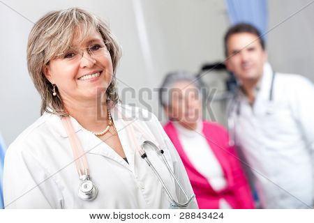 Geriatric female doctor smiling with an elder patient at the hospital