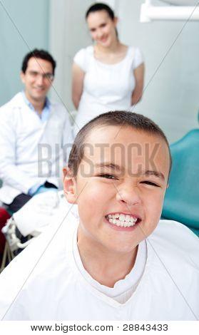 Kid visiting the dentist acting proud of his teeth
