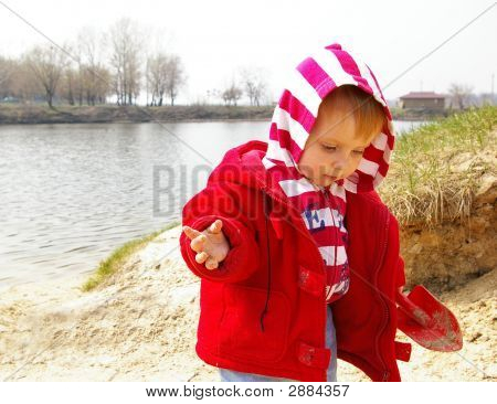 Little Girl Plays On Coast Of Lake