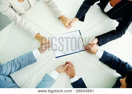 Image of businesspeople hands in hold with document in the center
