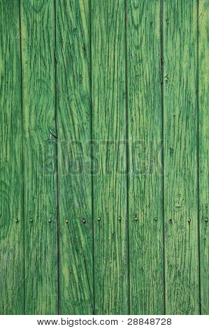 Green paint peeling from a wooden panel door. Aged texture