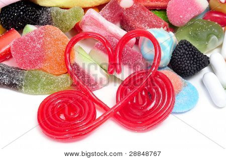 heart made with liquorice wheels and some candies on a white background