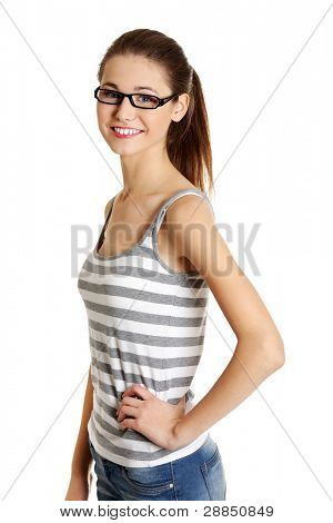 Site view portrait of a young female caucasian teen with glasses on her face smiling to the camera, on white.