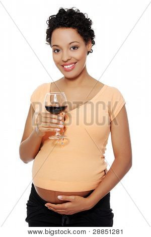 Front view of a pregnant woman holding a glass of wine, smiling to the camera, isolated on white background.