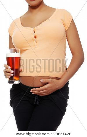 Front view of a pregnant woman holding a glass of alcohol next to her tummy, isolated on white background.