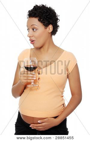 Front view of a pregnant woman holding a glass of wine, looking to the side, isolated on white background.