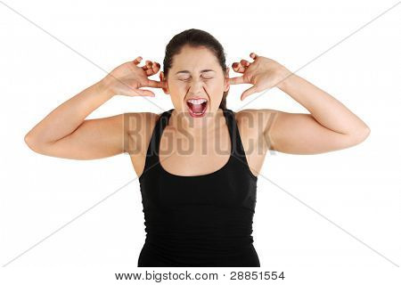 Front view portrait of a young angry female caucasian teen plugging her ears and shouting, on white.