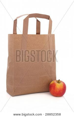 Red dessert apple next to a brown paper recycled shopping carrier bag isolated over white background.