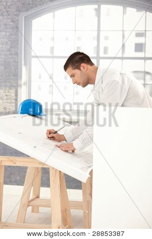 Handsome young architect drawing plans in office.?