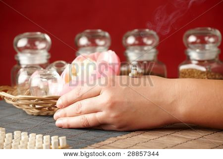 TCM Traditional Chinese Medicine. Smoking mini moxa stick, flower and natural herbs in glass jars in background.