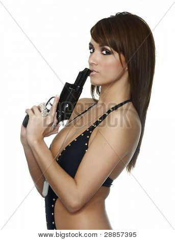 Young beautiful woman holding pistol gun blowing the end after shooting. Isolated against white background