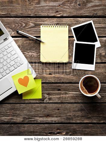 Portátil (notebook) con taza de café y papel pegajoso con Bloc de notas en mesa de madera vieja.