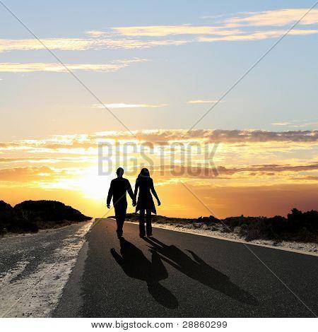 Man walking away at dawn along road