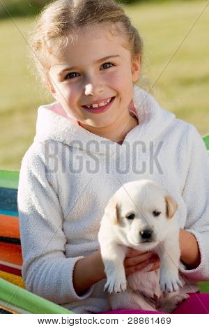 Happy childhood - little girl with cute Labrador puppy in hammock