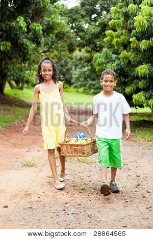 young kids carrying basket of apple in apple farm