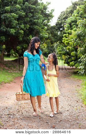 happy mother and daughter walking in fruit garden with basket of apple