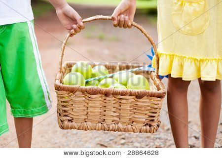 two children carrying a basket of apple outdoors