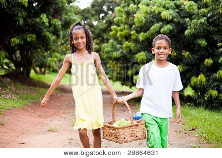 two happy kids carrying a basket of apple