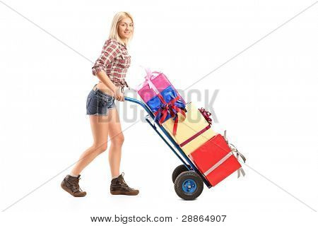 Full length portrait of a female manual worker pushing a handtruck with presents on it isolated on white background