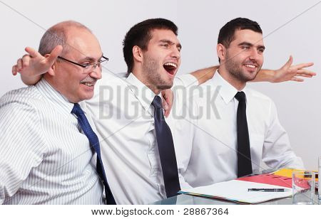 Three very happy and enthusiastic businessman during business meeting