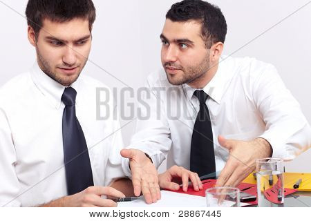 Two businessman have an argument over some paperwork.